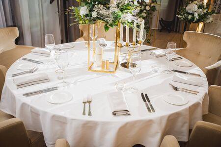 Glasses, flower fork, knife served for dinner in restaurant with cozy interior Stok Fotoğraf