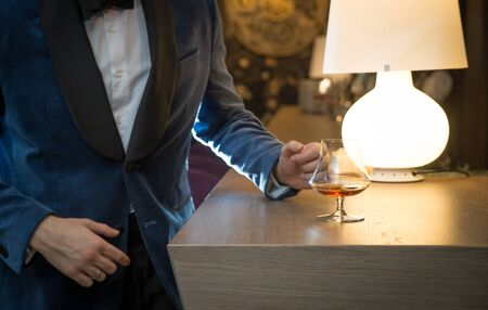 Handsome well-dressed man in jacket with glass of beverage Stok Fotoğraf