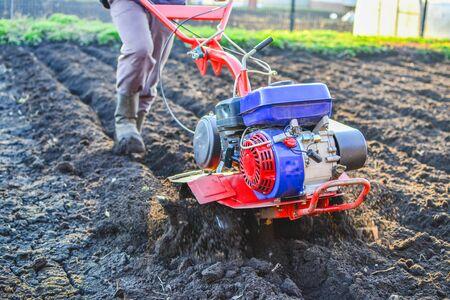Man professional gardener using plow at land with green grass in garden outdoor