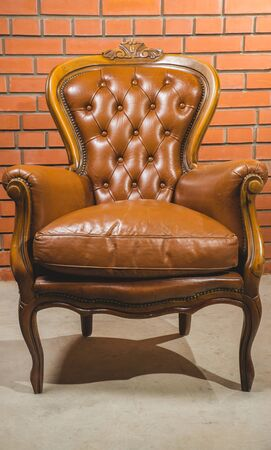 Antique armchair furniture with cushion against white wall Banco de Imagens