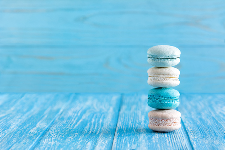 Delicious Macaroons on a blue wooden table closeup