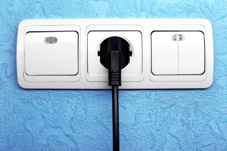 switch plug: Electrical switch,  plug and outlet connector in blue wall
