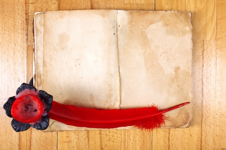 vintage Message Book with red feather pen and candle on table photo