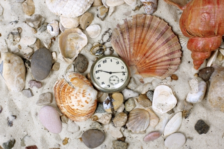 time for vacation - Sea Shells and vintage clock on sand photo