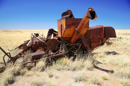 vintage rusty abandoned combine harvester in old field, Arizona, USA