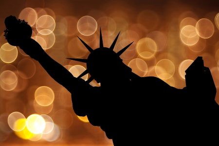 silhouette NY Statue of Liberty against light circle as fireworks or night city photo