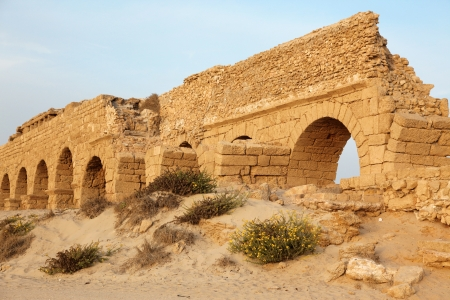 Sundown at old Ancient Roman aqueduct in Ceasarea at the coast of the Mediterranean Sea, Israel