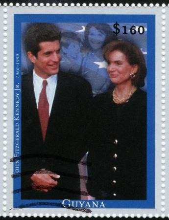 john fitzgerald kennedy: GUYANA - CIRCA 1999 : stamp printed in Guyana shows John Fitzgerald Kennedy Jr (L) American socialite, lawyer, elder son of U.S. President John F. Kennedy with mom Jacqueline , circa 1999 Editorial