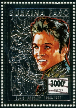 BURKINA FASO - CIRCA 1997 : stamp printed in Burkina Faso shows rock and roll singer and actor Elvis Presley, silver stamp, circa 1997 Stock Photo - 15837497