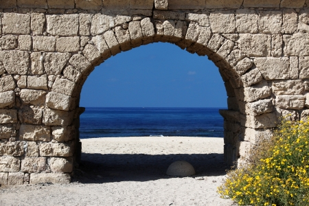 Ancient Roman aqueduct in Ceasarea at the coast of the Mediterranean Sea photo