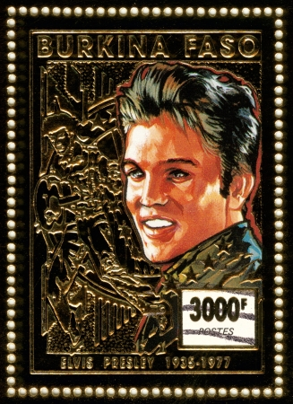 BURKINA FASO - CIRCA 1997 : stamp printed in Burkina Faso shows rock and roll singer and actor Elvis Presley, golden stamp, circa 1997 Stock Photo - 15854809
