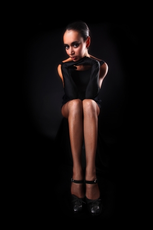 ady: girl with long legs against black background