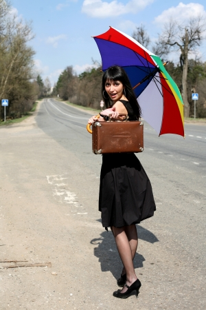 girl with vintage suitcase and umbrella outdoors photo