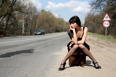street fashion: girl in the road sit atop vintage suitcase