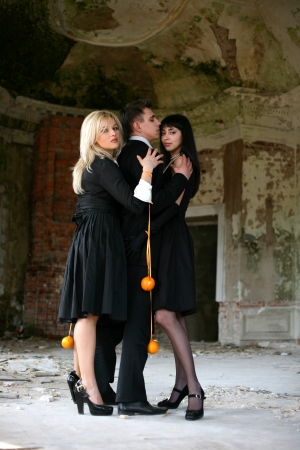two girl with oranges and man inside vintage house photo