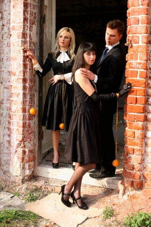 two girl with oranges and man beside old house photo