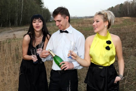 two girl and man with wine outdoors Stock Photo - 15940578