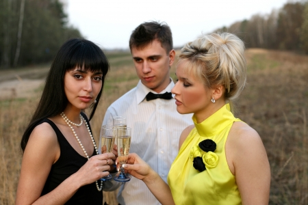 human sexual activity: two girl and man with wine outdoors Stock Photo