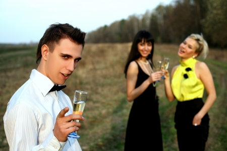 two girl and man with wine outdoors Stock Photo - 15928217