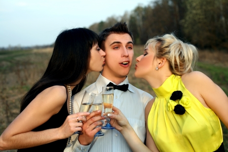 two girl with wine kissing man outdoors photo