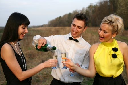 two girl and man with wine outdoors Stock Photo - 15928293