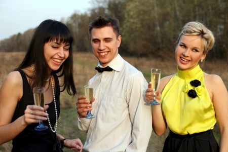 two girl and man with wine outdoors Stock Photo - 15928352