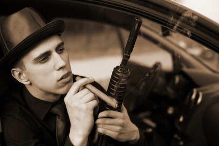 killing cancer: man in car with cigar and rifle Stock Photo