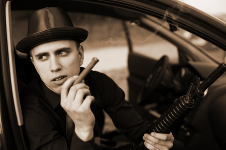 man in car with cigar and rifle photo