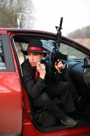 joven fumando: hombre en el coche con el cigarro y el rifle Foto de archivo