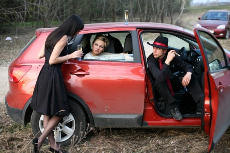 brunette , man and woman with cigar, wine in car photo