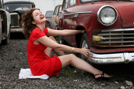 girl beside retro car  - under constructions to wheel photo