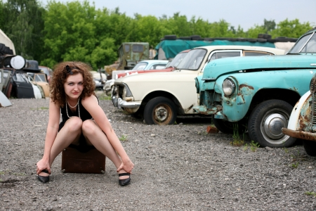 atop: girls beside retro car sit atop in vintage suitcase Stock Photo