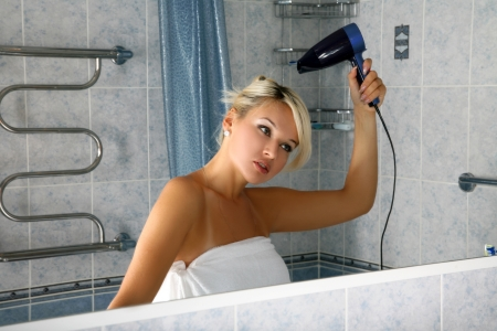 blow drier: girl in bathroom with drier Stock Photo