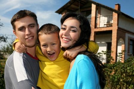 Joven familia feliz junto a su nueva casa Foto de archivo - 15980302