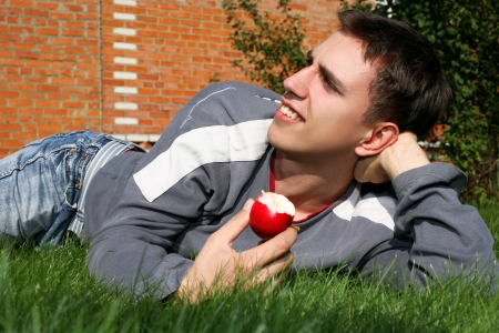 Young happy man with apple beside brick wall photo