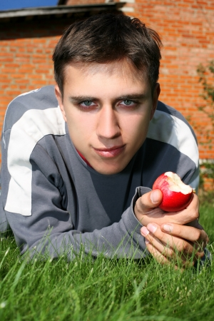 man in green grass with apple photo