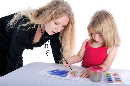beside table: mom and daughter with paint beside table isolated on white Stock Photo