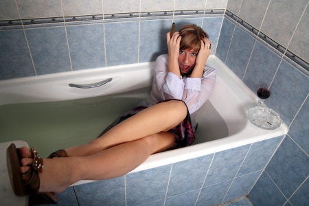 terribly: fright-bathroom, blonde in clothes with a beaker of wine and cigar Stock Photo