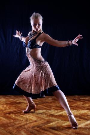 Tänzerin in Ballsaal vor schwarzem Hintergrund