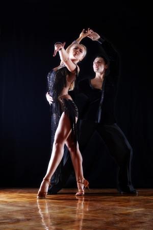 ballroom dance: dancers in ballroom against black background