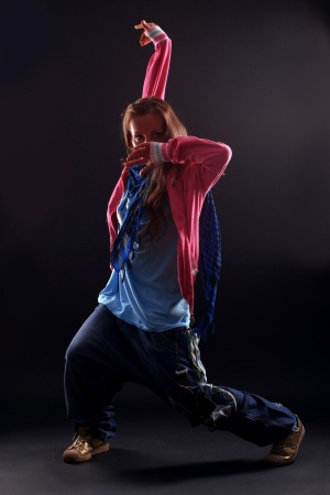 Hip hop woman dancer against black background photo
