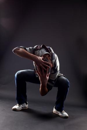 Hip hop man dancer against black background photo