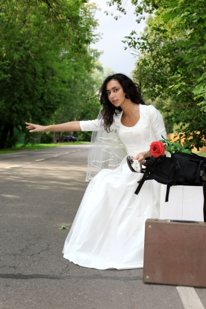 beautiful bride hitch-hike at the road Stock Photo - 15980393