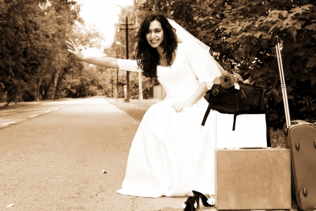 beautiful bride hitch-hike at the road photo