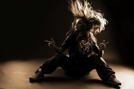 salto largo: mujer moderna bailarina contra negro Foto de archivo