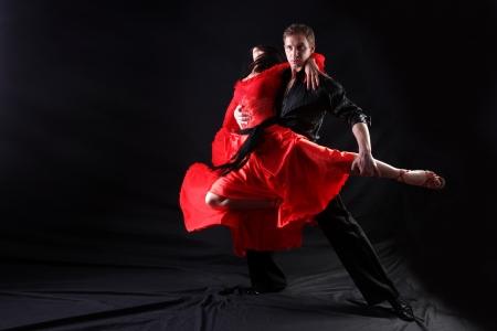 baile latino: bailarines en acción contra el fondo negro Foto de archivo