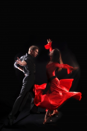 latin dancing: dancer in action against black background Stock Photo