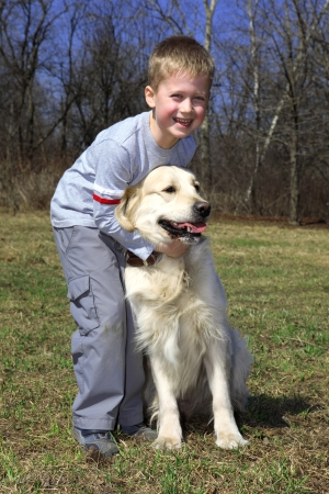 endearing: friends - little boy with big retriever outdoors