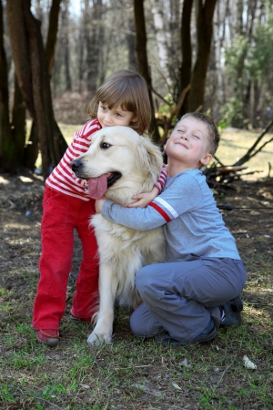 trusting: friends - children with retriever outdoor Stock Photo