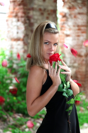 lovely woman with rose under falling petals Stock Photo - 15980422